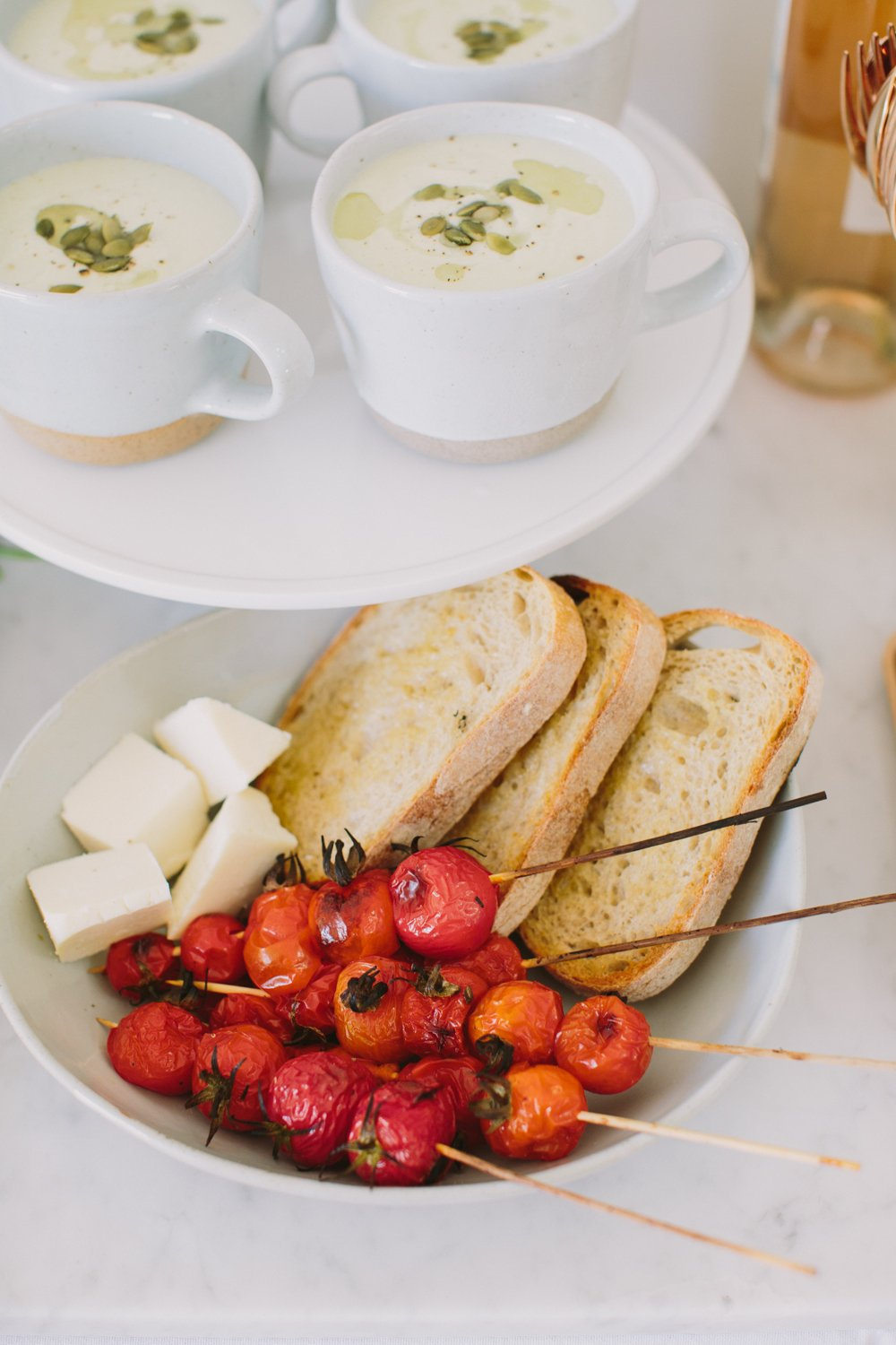 Crostini, mozzarella and roasted tomatoes in a bowl next to a tray of creamy white soup in mugs