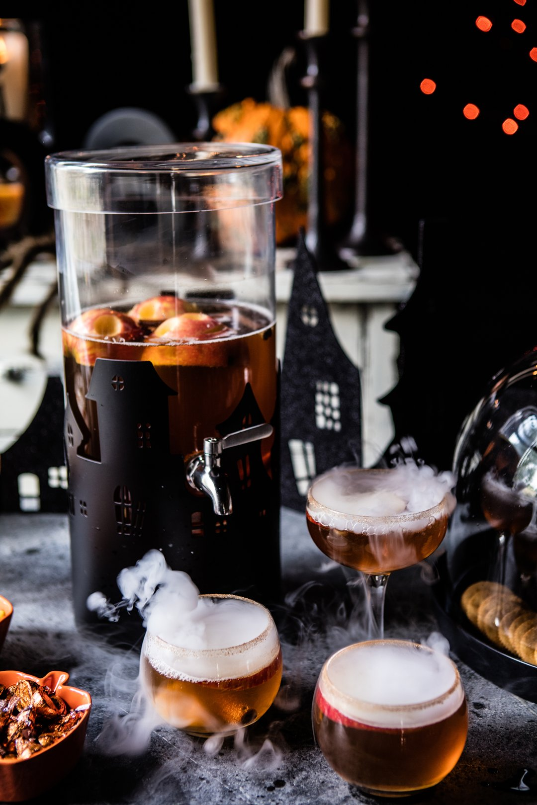 Halloween-themed drink dispenser filled with apple punch, surrounded by smoking cocktail glasses