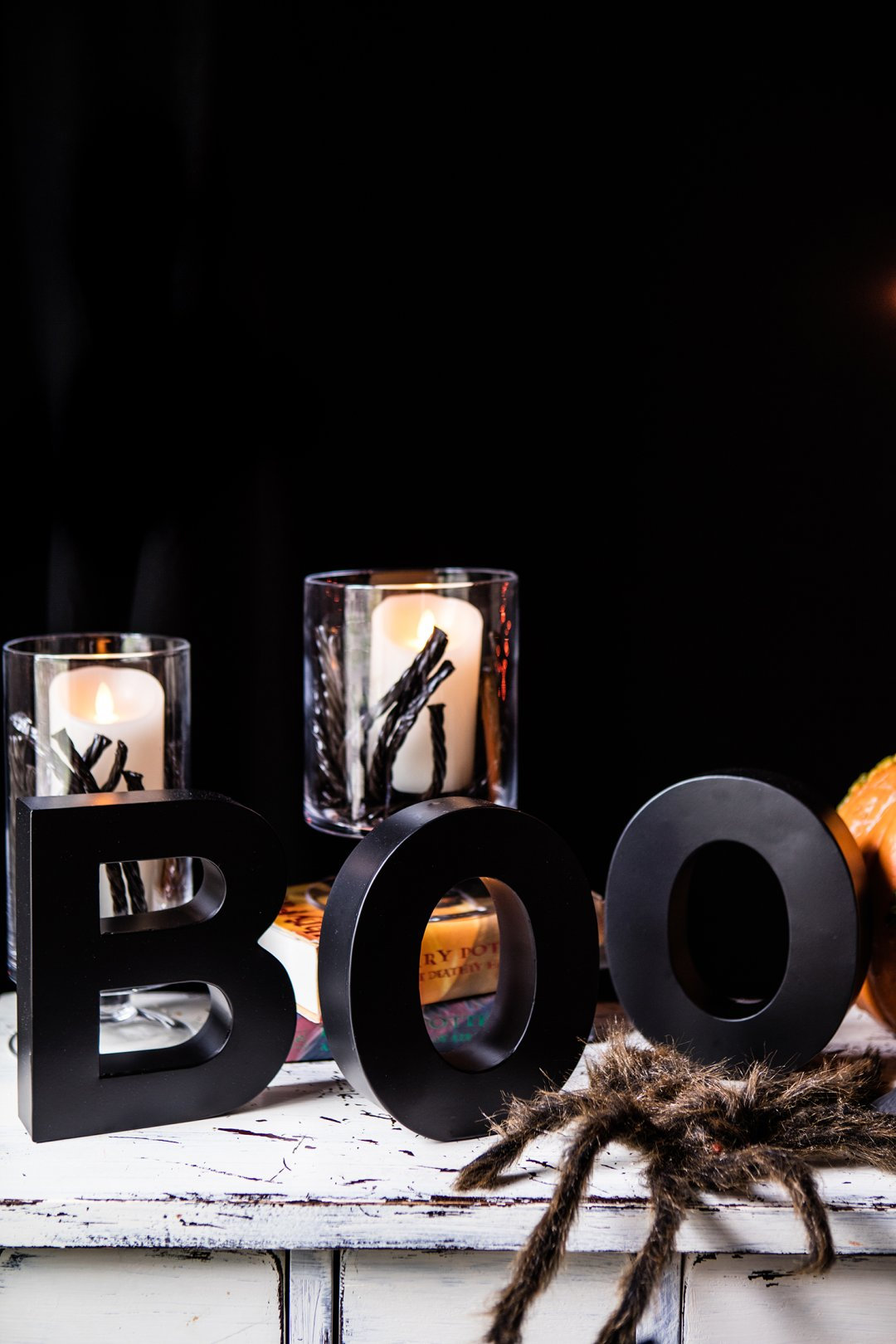 Halloween table decorations including candles in glass hurricanes and black standing letters spelling boo