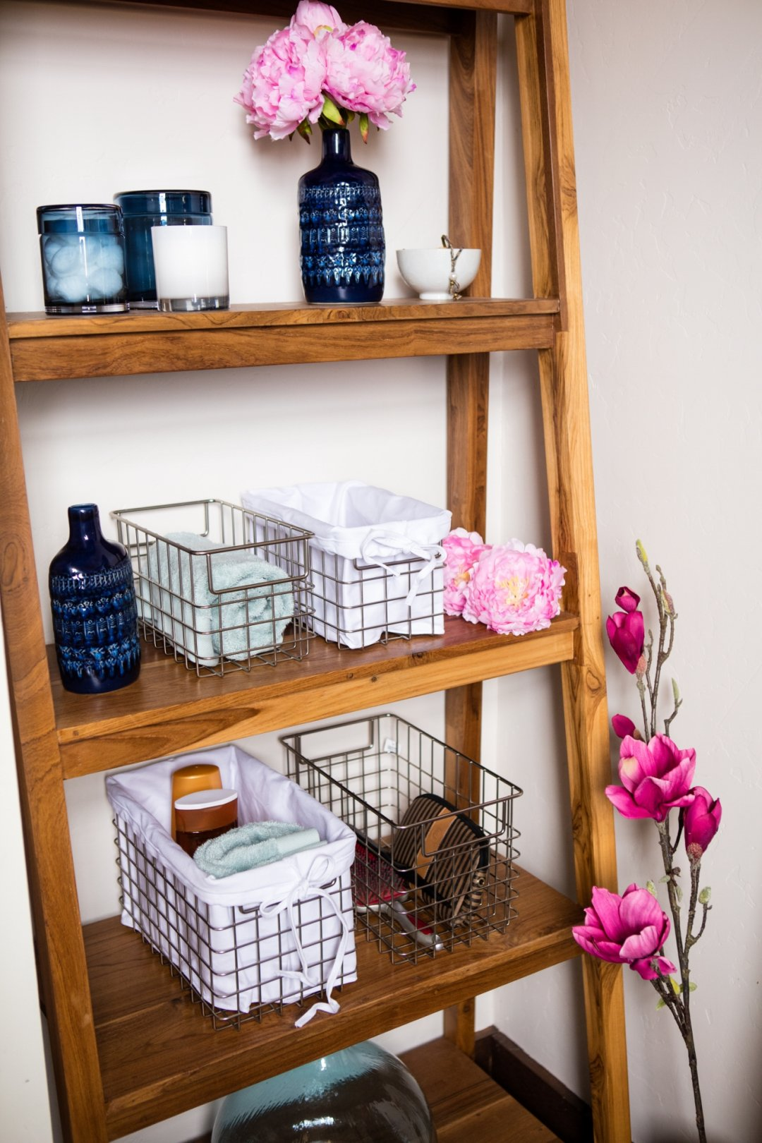 Wooden shelf with wire baskets and glass canisters for organization