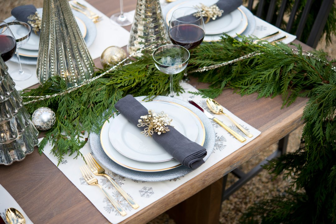 set of plates and a napkin surrounded by a tree branch, glass trees and a glass of wine