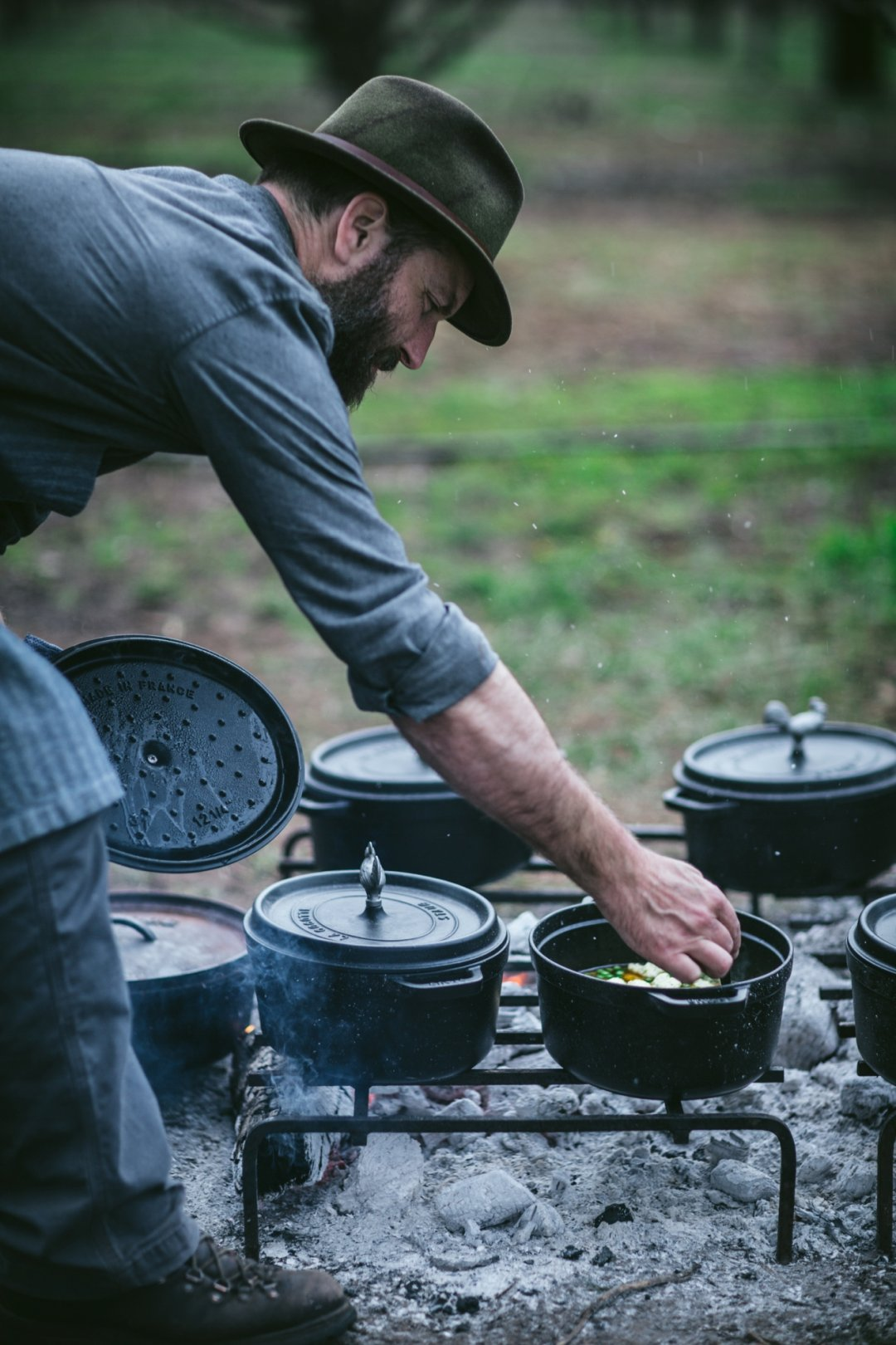 Man checking on pot of food over grill built into ground with other pots cooking