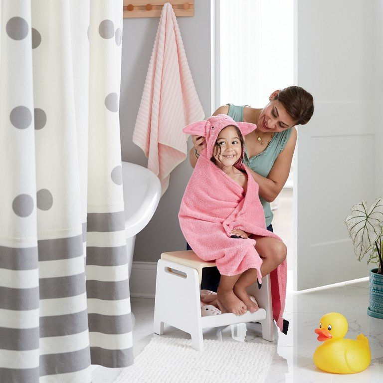 In a bathroom, a girl is wrapped in in a hooded towel next to her polka dot shower curtain