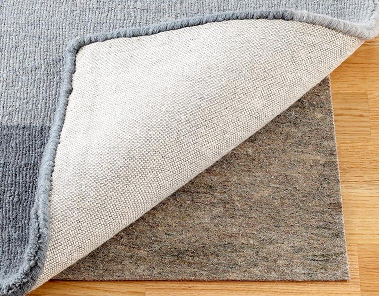A high quality rug pad is shown beneath a folded rug.