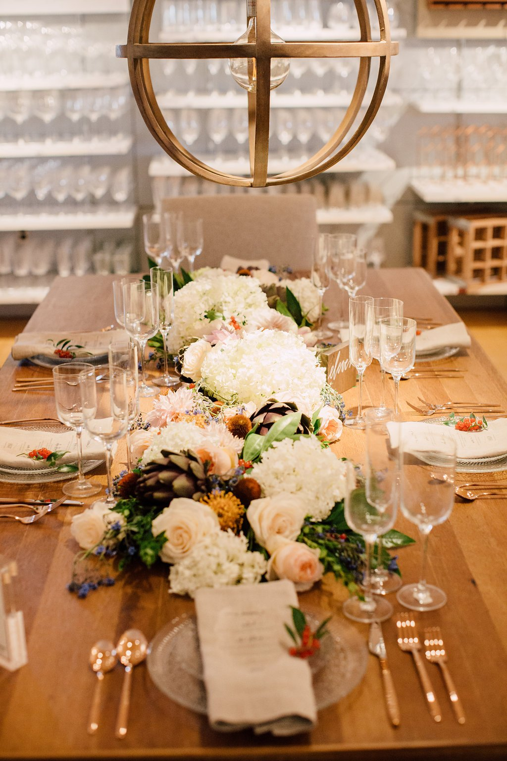Set table with floral centerpiece and brass chandelier over head