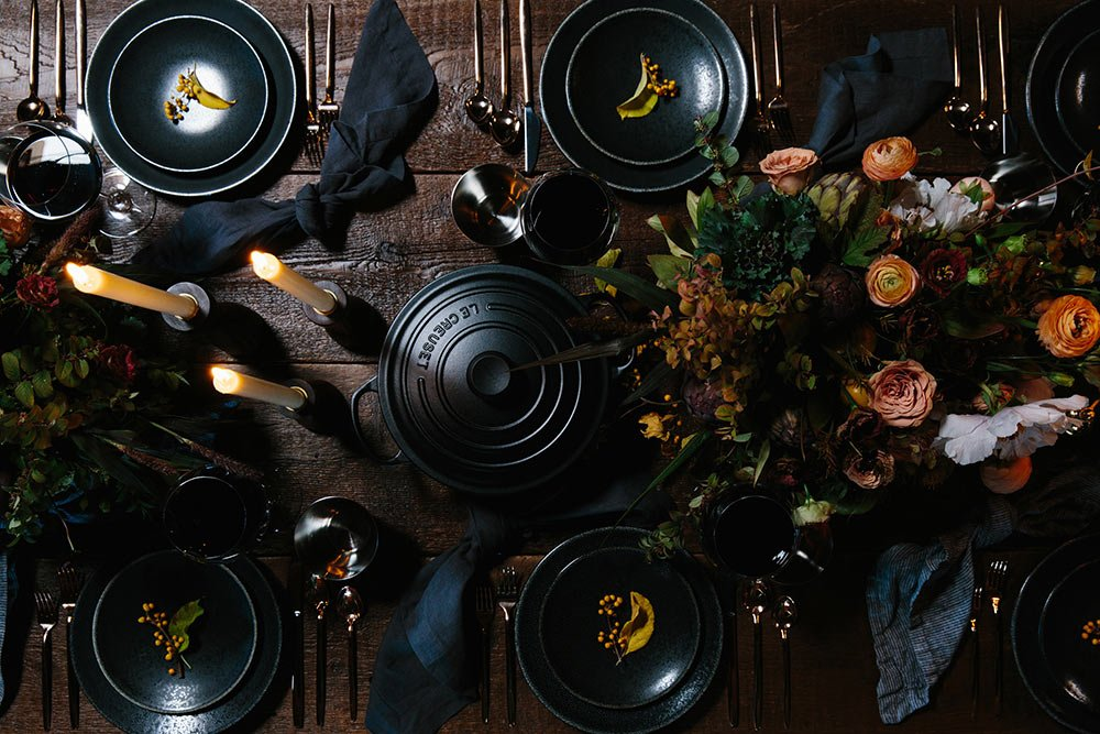 Black place settings around a black Le Creuset French oven on a wood Thanksgiving table