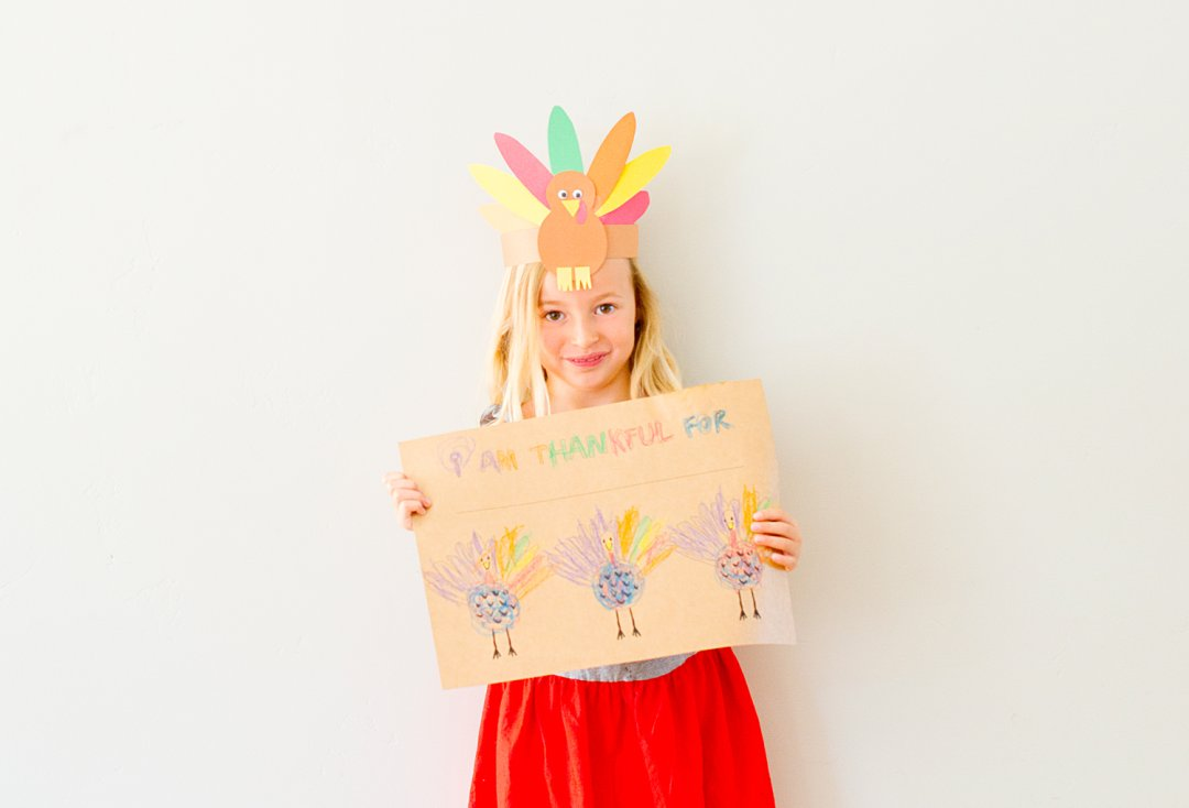 Girl holding colored construction paper Thanksgiving sign and wearing a paper turkey headband