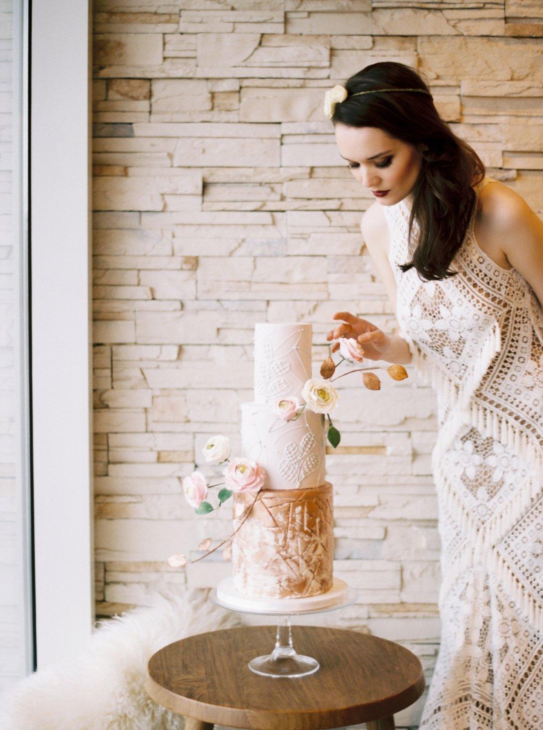 Bride in boho style wedding dress standing next to three tier cream wedding cake