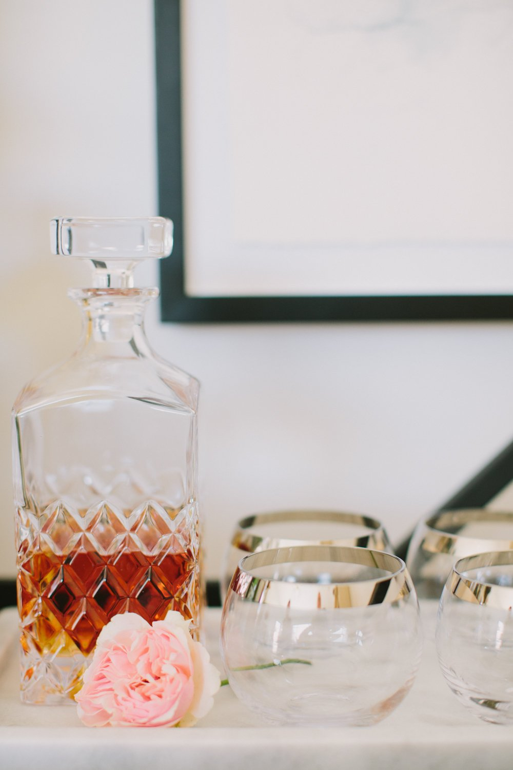 Marble serving tray on barcart with cocktail glasses and a clear glass liquor decanter