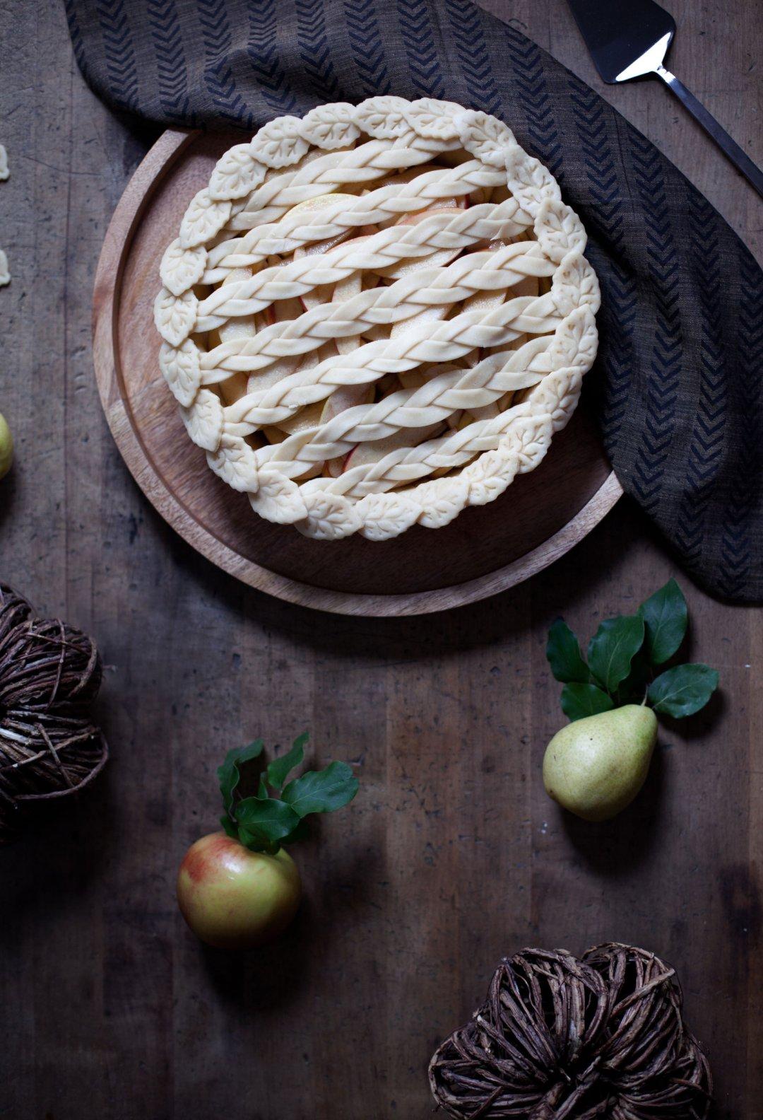Cross-hatch pie crust pattern on an raw pie on a wood countertop