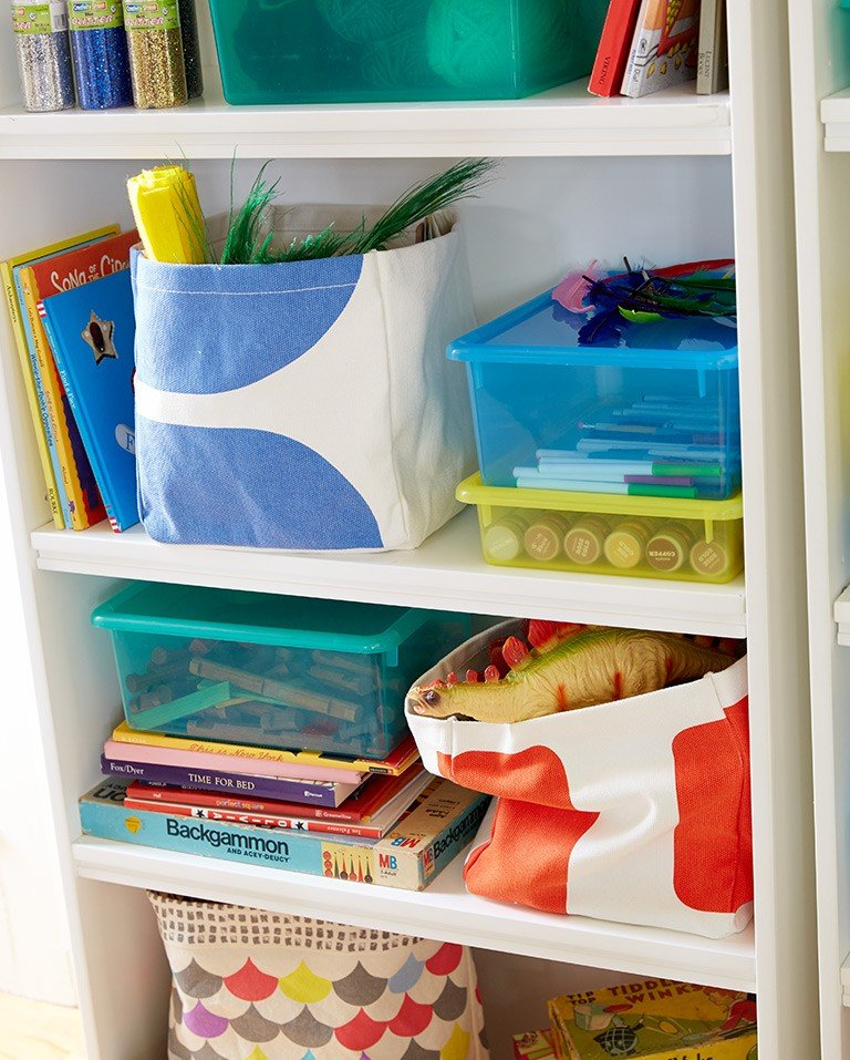 A shelf is stacked with storage bins, toys and games.