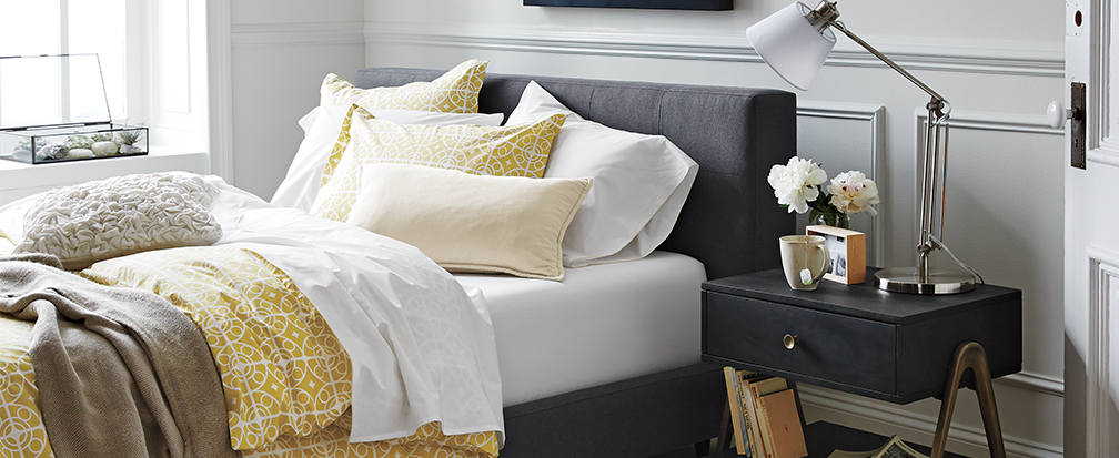 Bed with yellow and white sheets on a grey frame next to a bedside table with a lamp and mug of tea