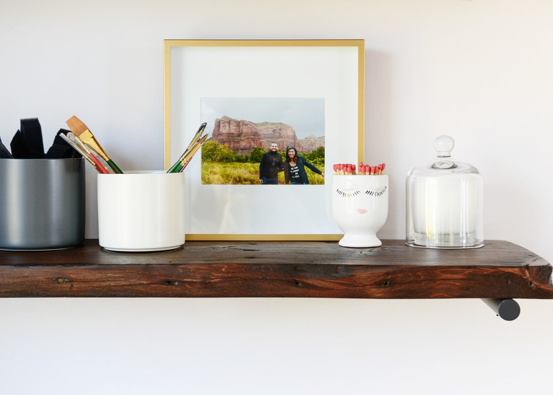 Dark-stained wood shelf decorated with a family photo and a couple of white ceramic cannisters holding paint brushes and matches