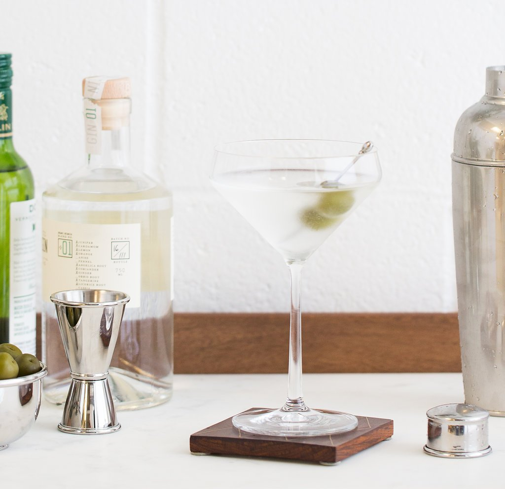 dirty martini containing two olives that is placed on a coaster on a cabinet surrounded by martini accessories