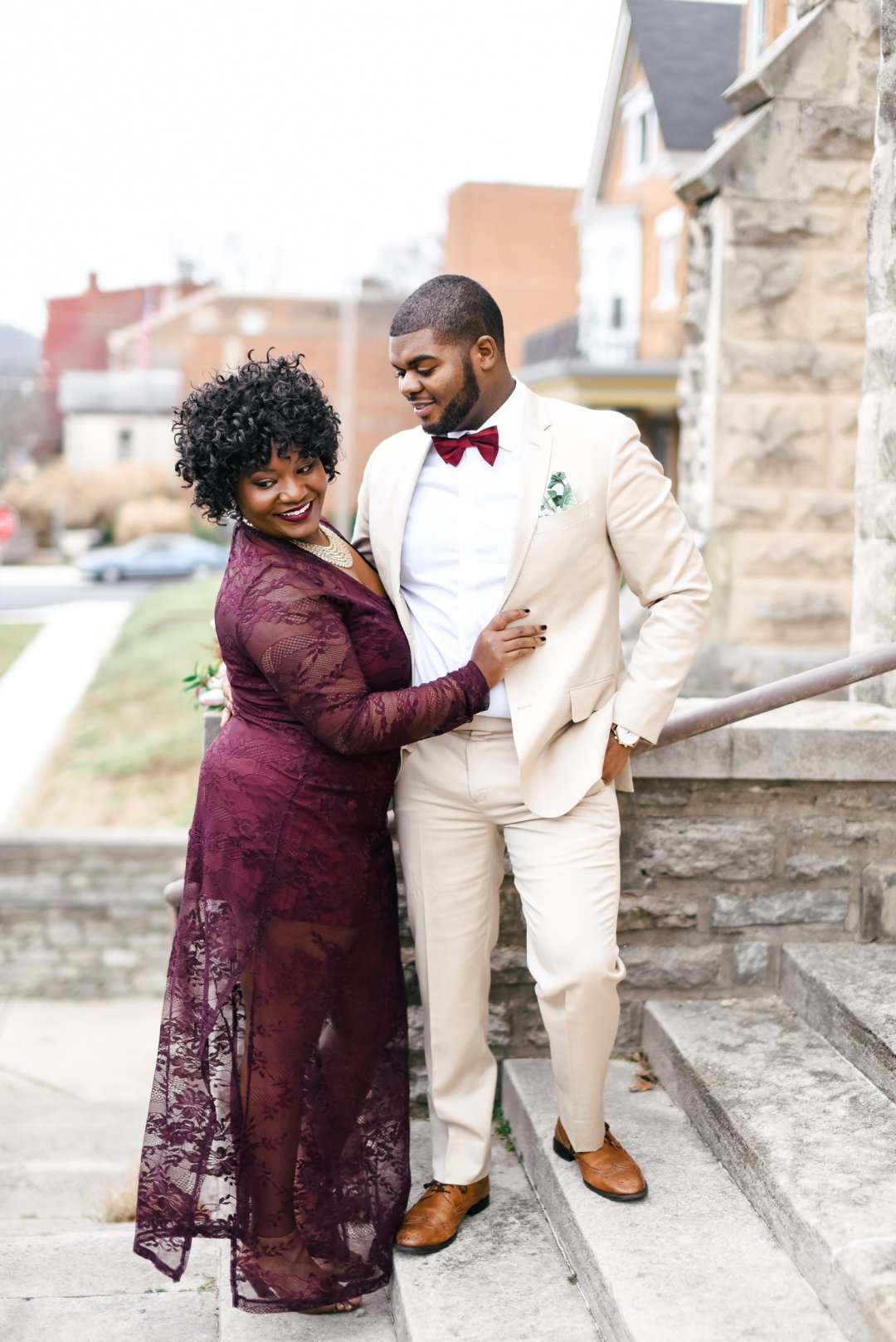 Groom standing on steps in cream suit with woman in burgundy dress