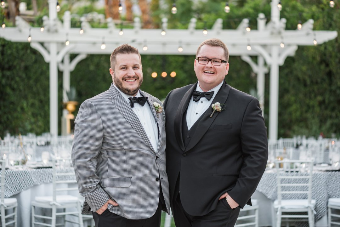 Two grooms with checkered and black tuxes at wedding