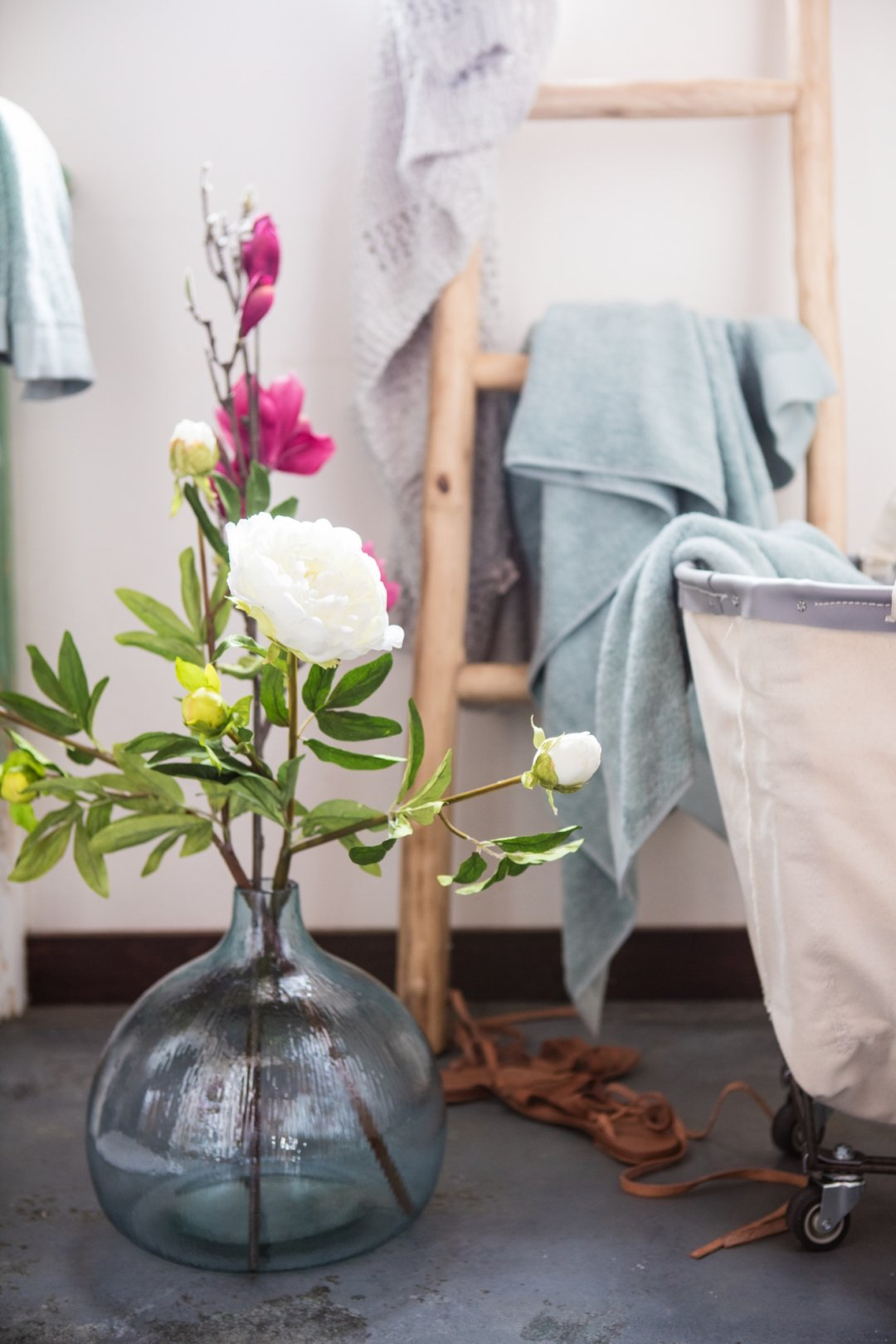 Flowers in blue vase next to ladder with towels
