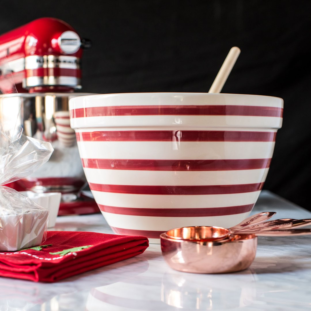 Red and white striped mixing bowl next to red christmas dish towels and copper measuring cups on a marble countertop