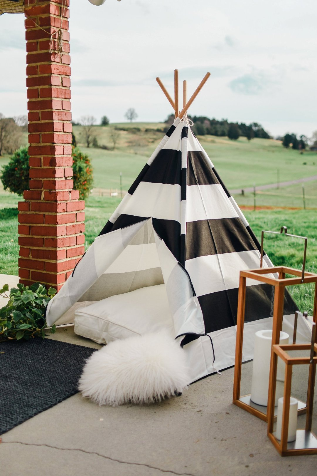 View of black and white striped teepee with lanterns to the right