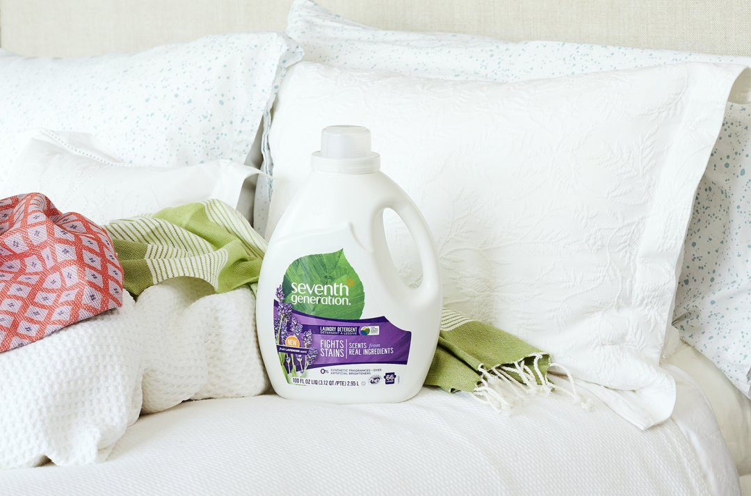 laundry bottle on bed against pillows and covers