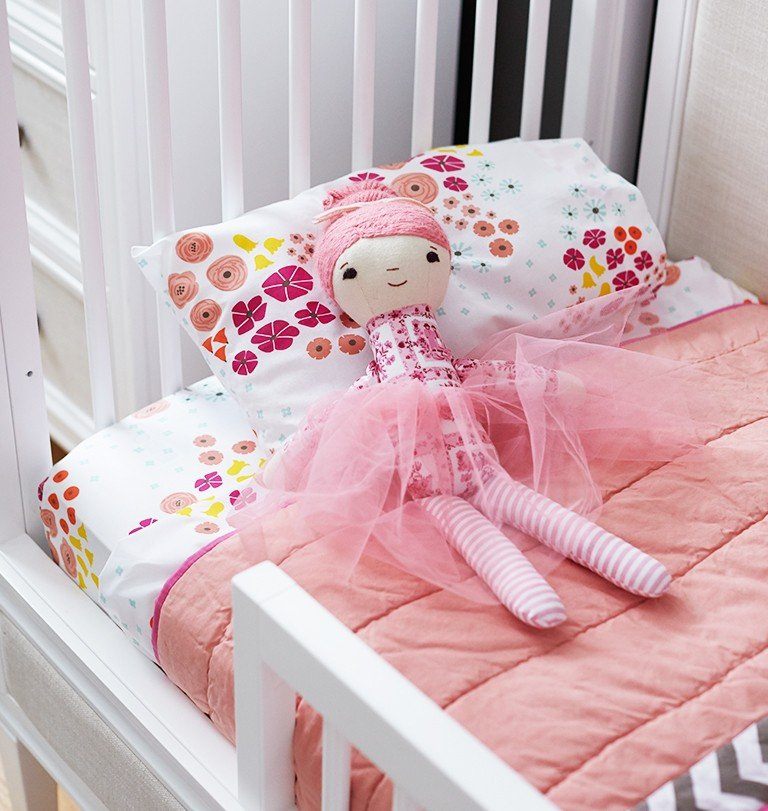 A toddler bed has floral bedding and a ballerina doll.