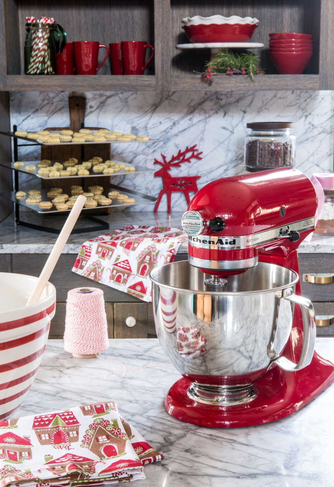 Red KitchenAid mixer on marble countertop in kitchen decorated for Christmas
