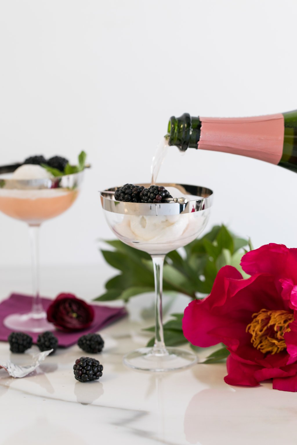 Pouring champagne into coupe glass with sorbet