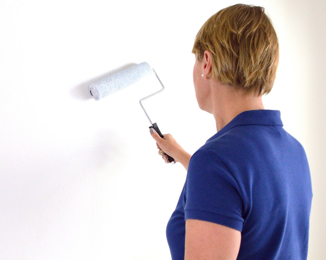 Woman priming a wall with white paint and a paint roller