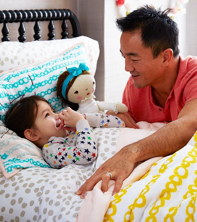 A dad tucks his daughter into bed with her doll.