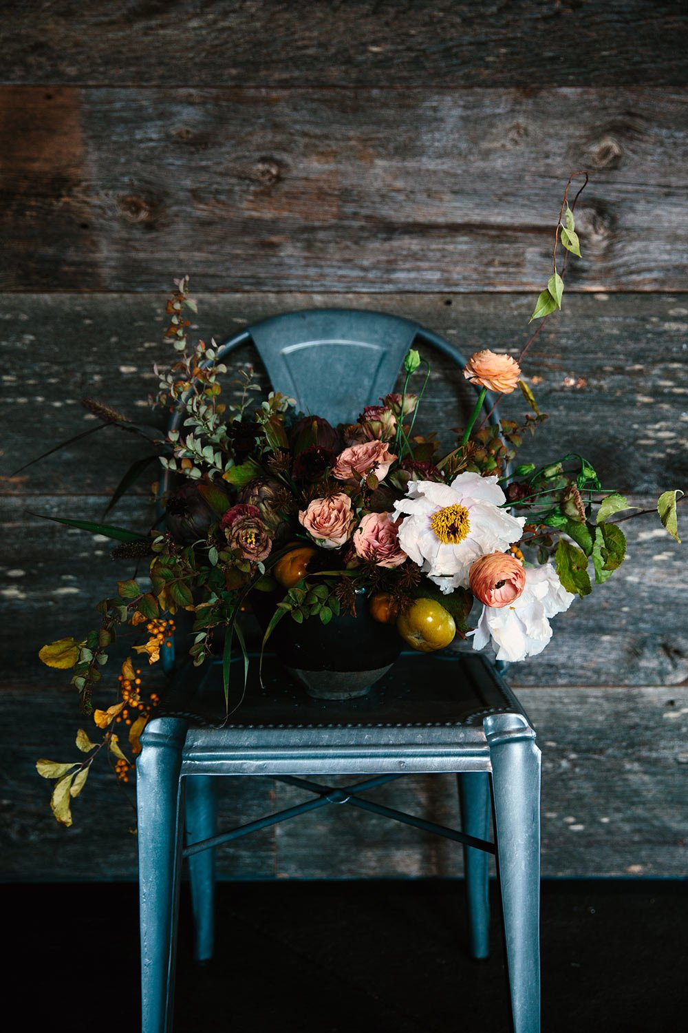 Fall bouquet with pinks and greens in a short vase on a metal dining chair