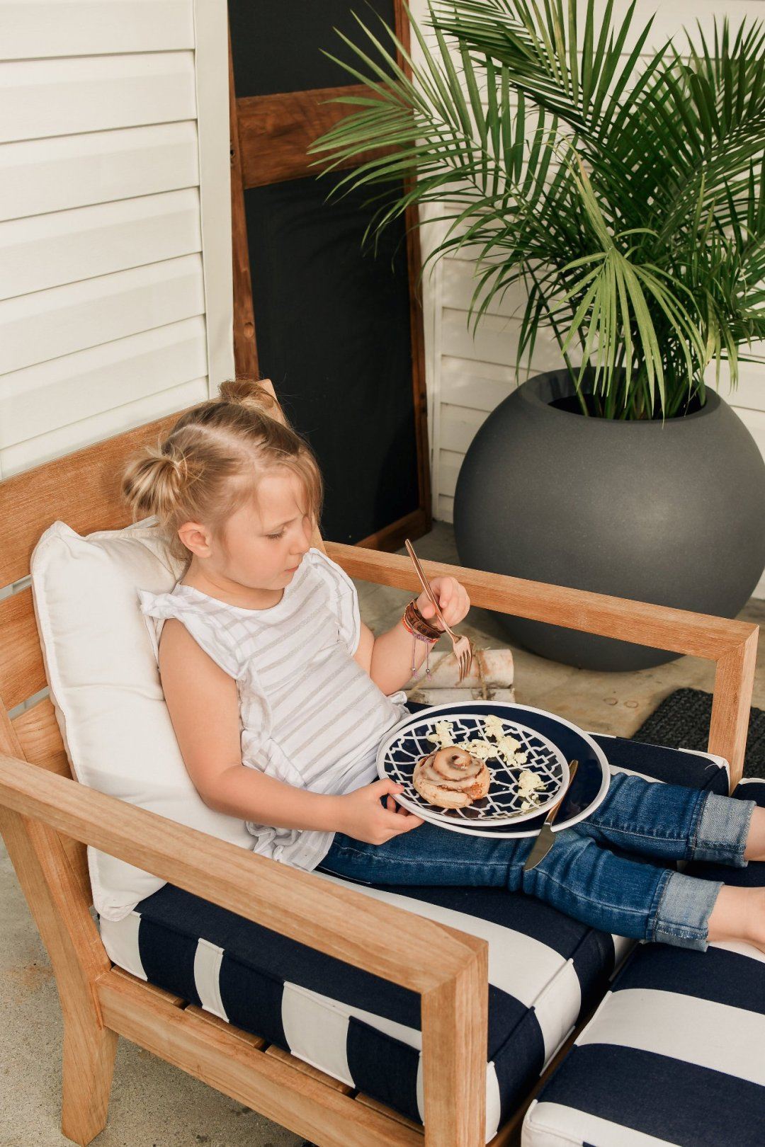 Little girl eating cinnamon roll on chair with potted plant in background