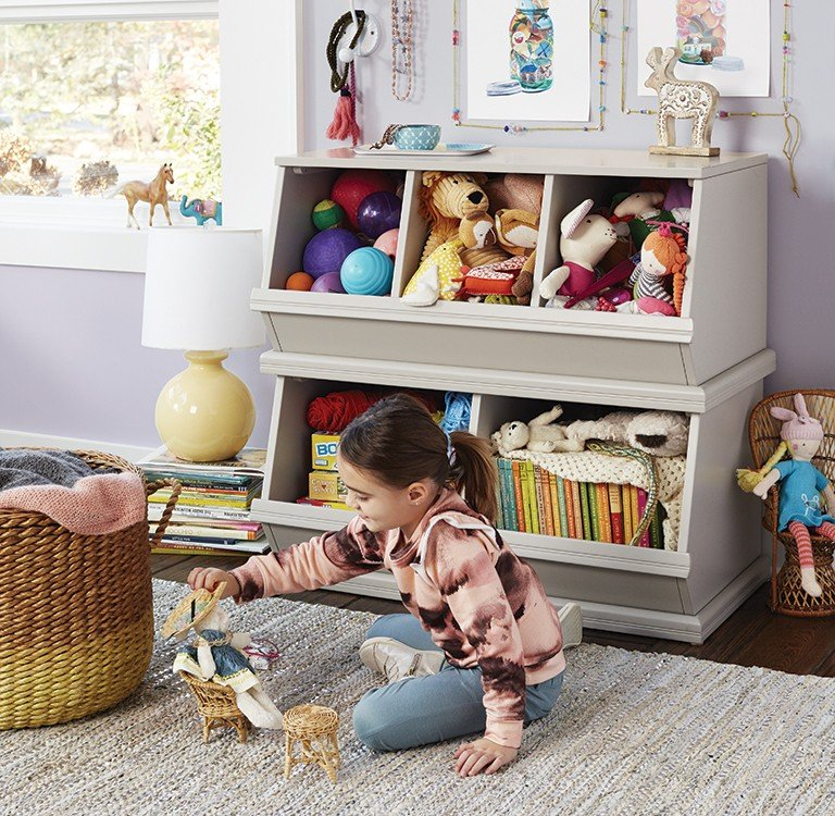 A young girl plays near her toy boxes filled with stuffed animals, books and games.