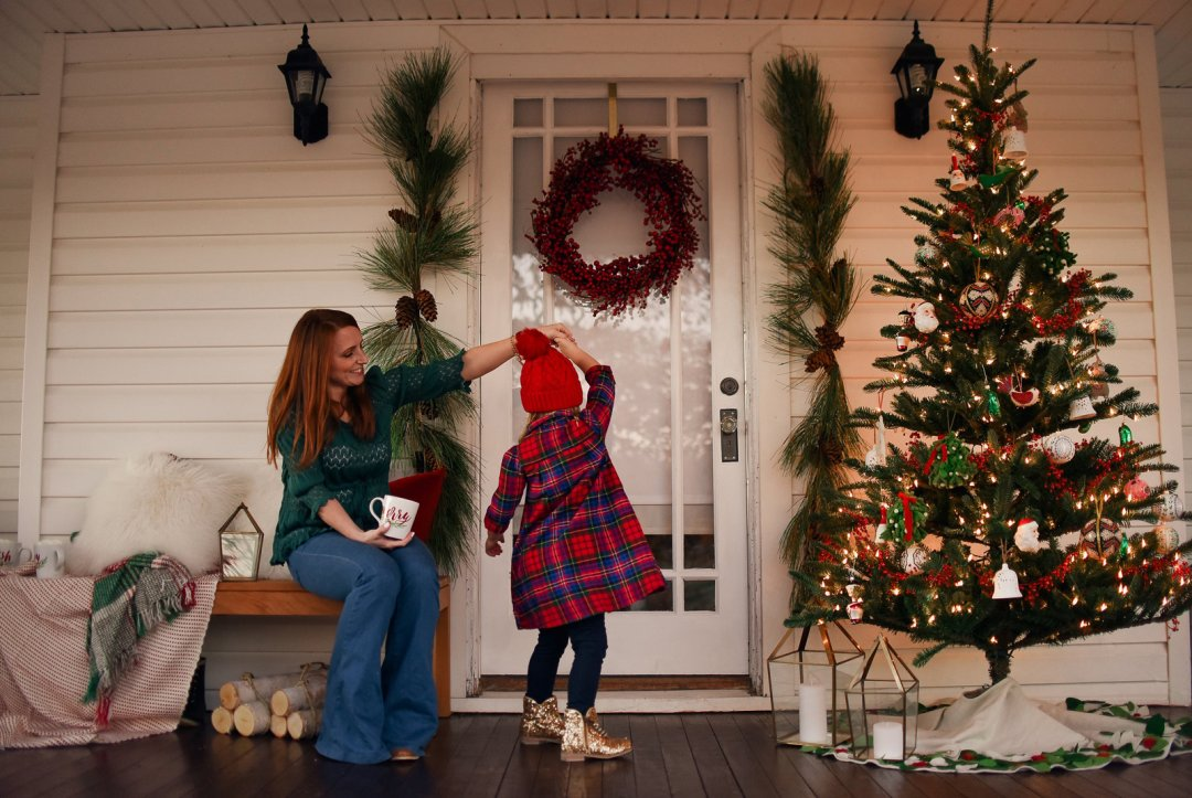 Mother and daughter dancing on front porch decorated for Christmas