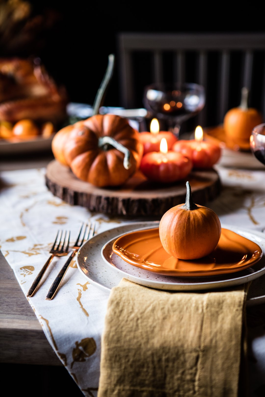 Thanksgiving place setting topped off with a small decorative pumpkin
