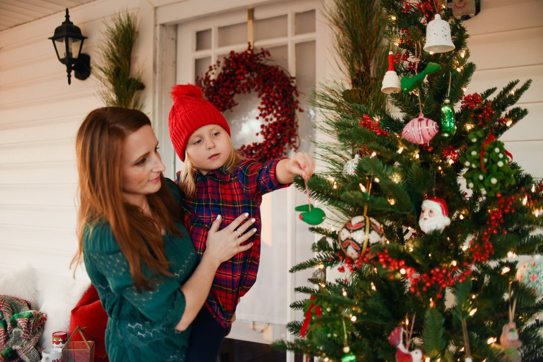 Mother holding daughter so she can decorate Christmas tree on porch with ornaments