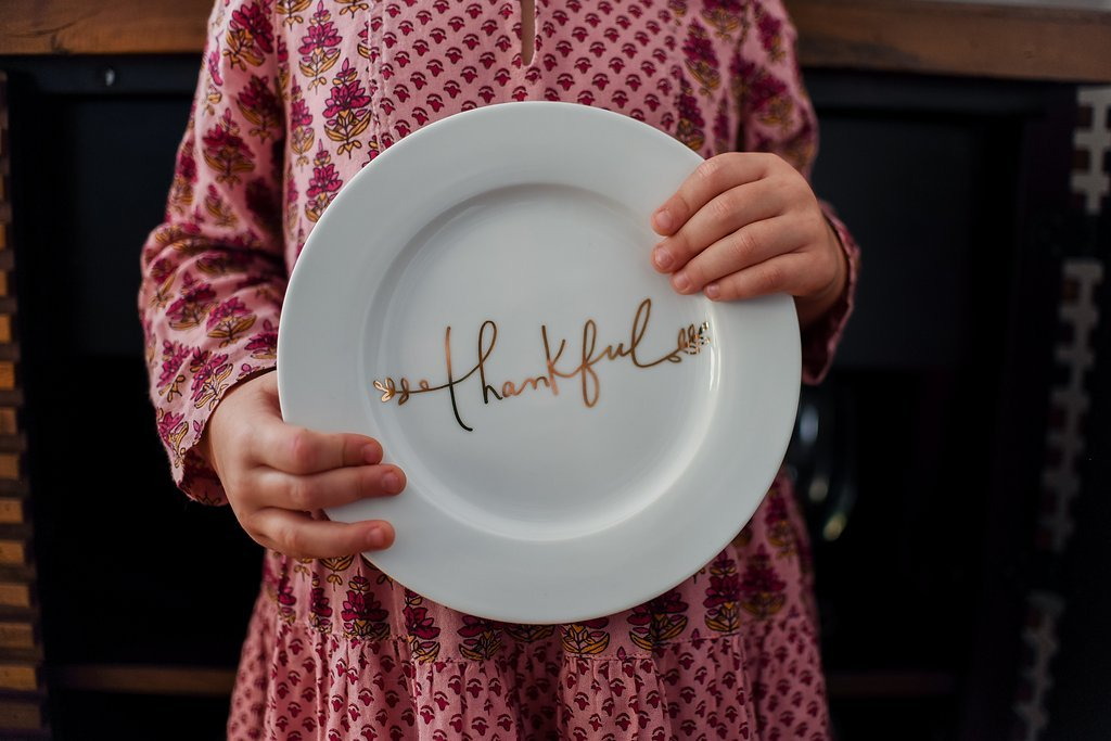 Girl holding a white dinner plate with the word thankful written across it in gold script