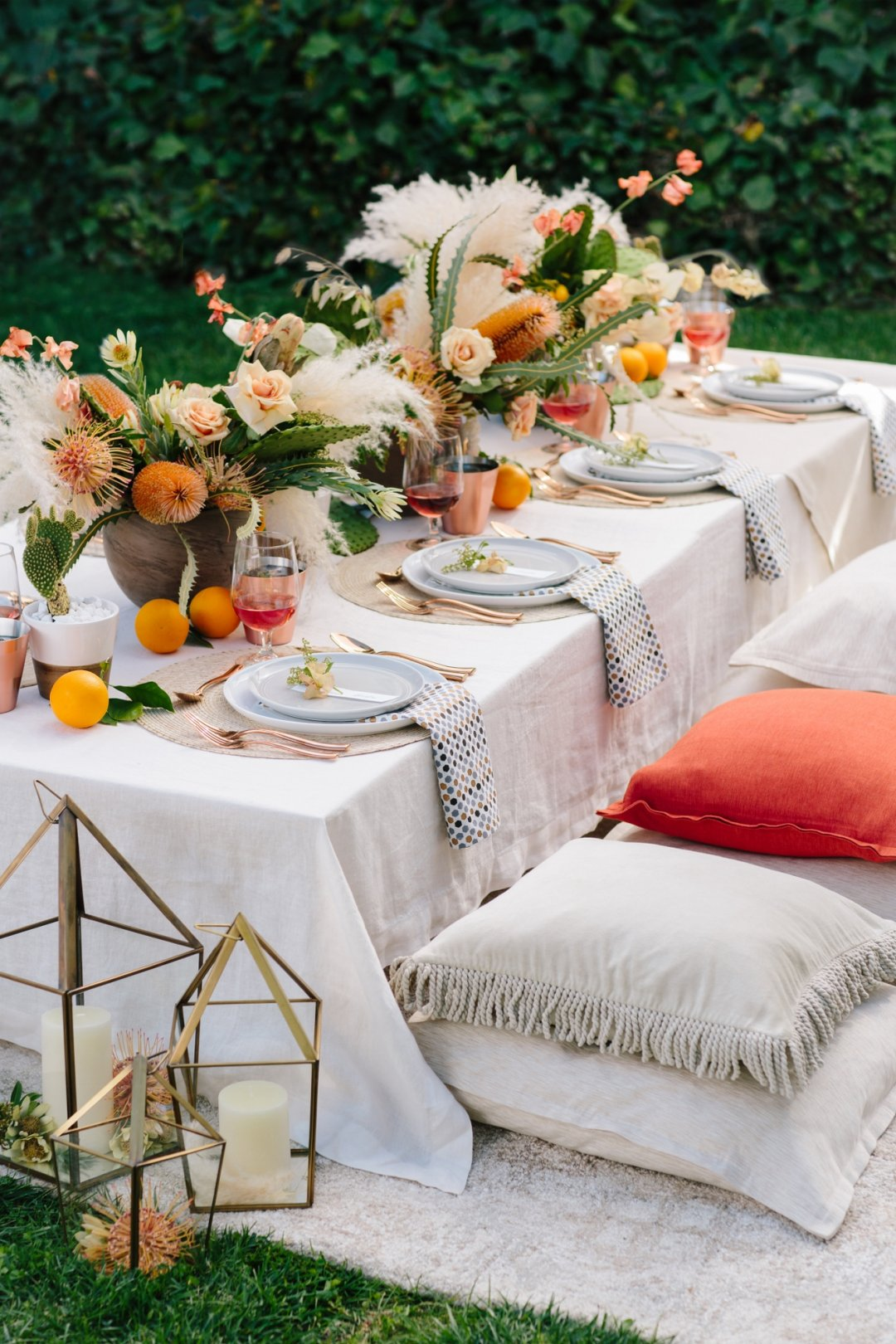 Side view of table set for party, with pillows as seats and lanterns near by