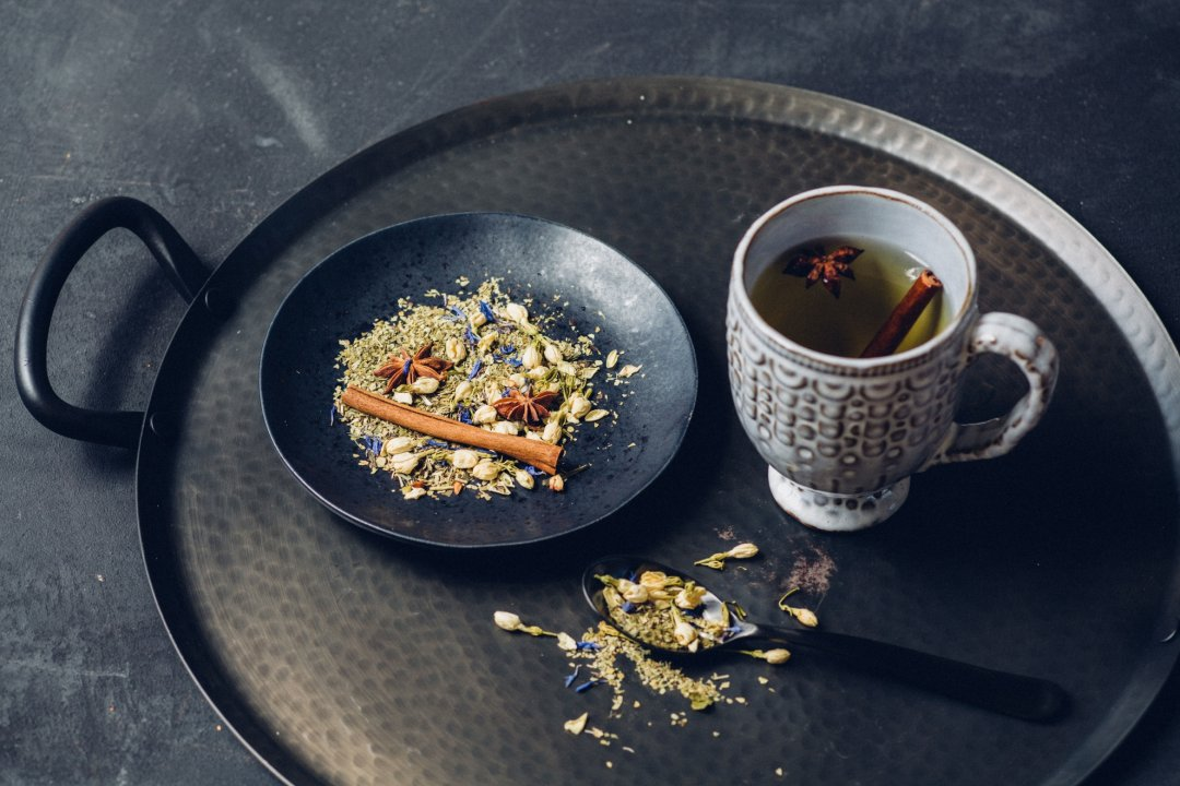 Black plate on metal tray with herbs, next to artisan mug with tea and spoon with herbs