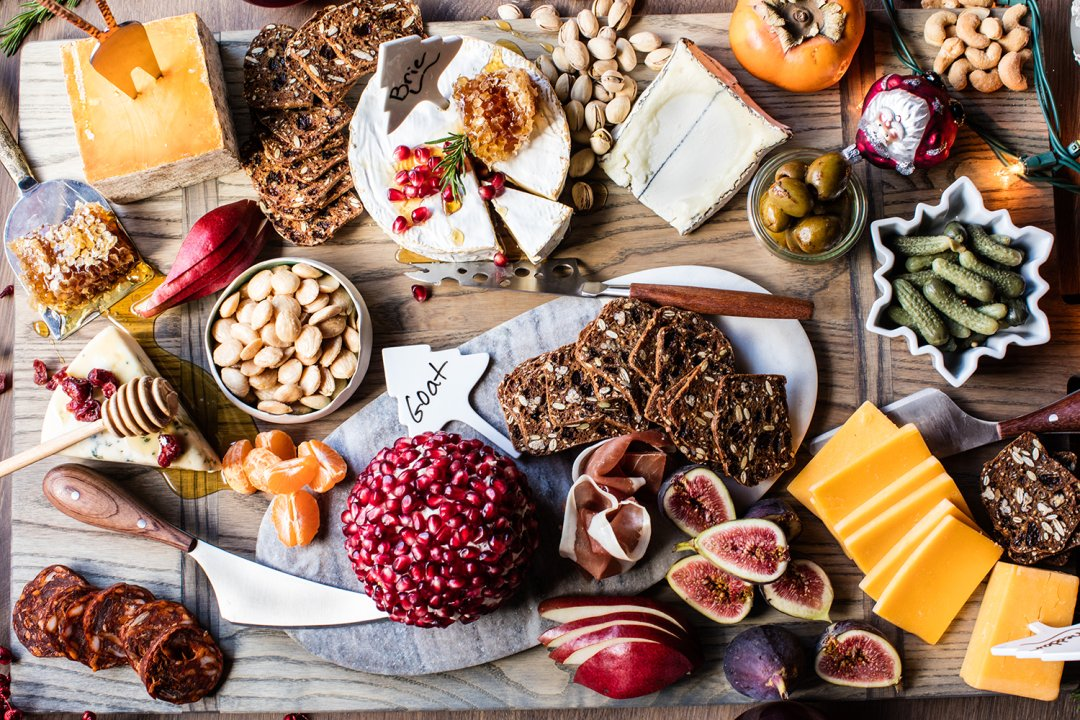 Holiday charcuterie board filled with cheddar, goat and brie cheeses and bowls of nuts, fruits and other toppings