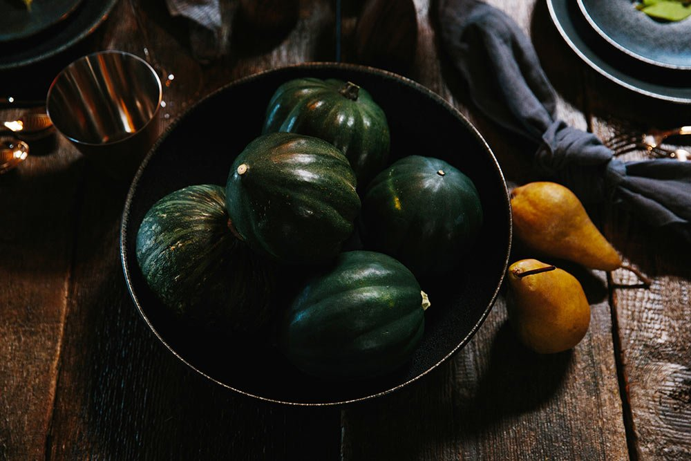 Green gourds in a black dinnerware bowl on a wood table
