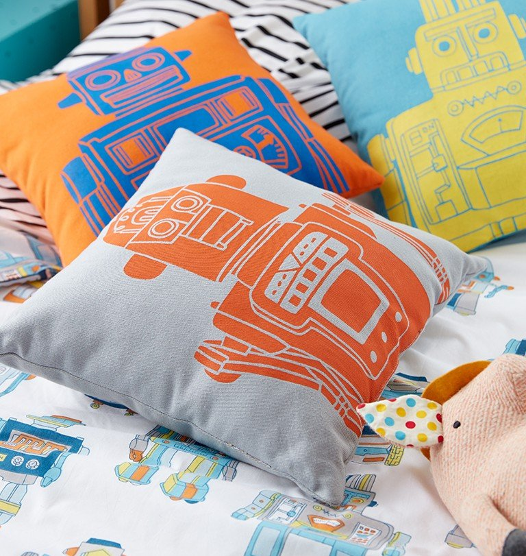 Robot throw pillows sit on a boys bed.
