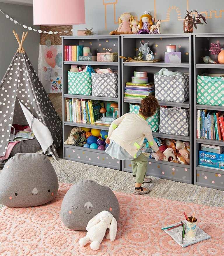 A girl plays near a wall of bookshelfs with storage bins for toys.