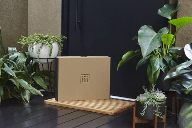 Black Tux box sitting at door of home