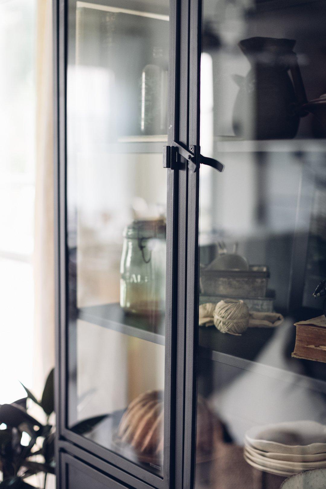 Tall black cabinet displaying keepsakes