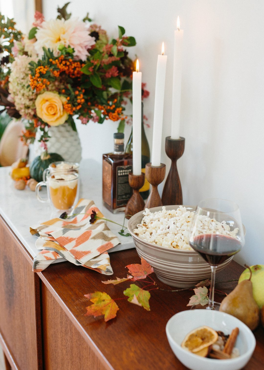 Popcorn and wine laid out on a sideboard decorated for fall with leaves and candles in wooden candle holders