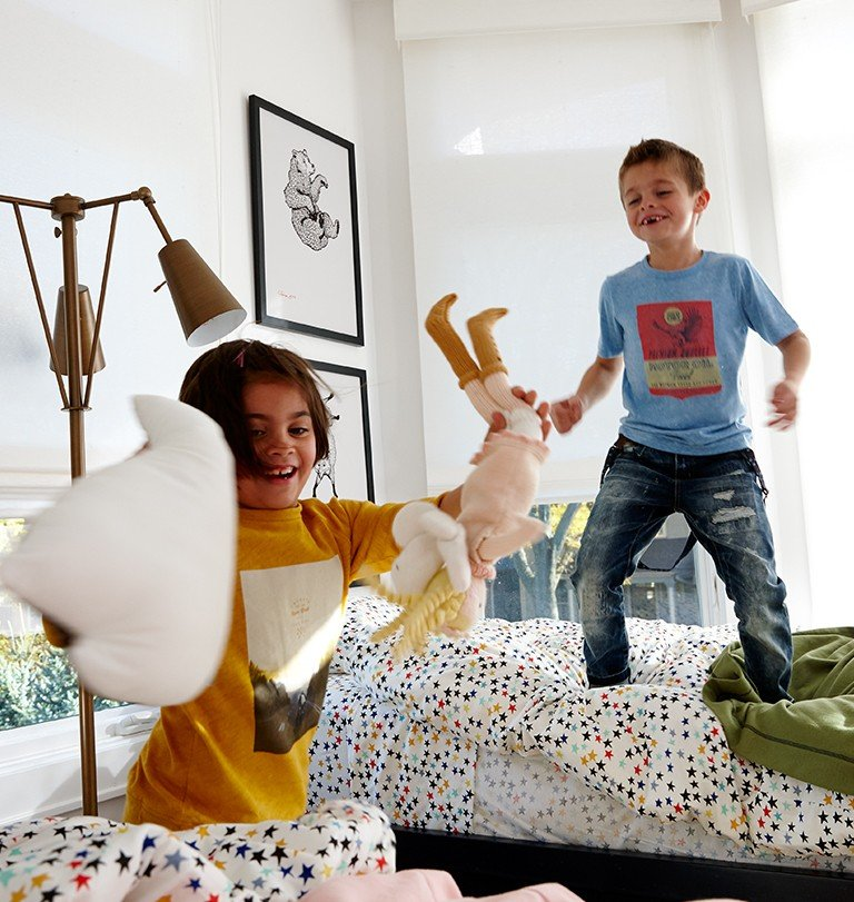 Kids play and jump on their bed, which is covered with star sheets.