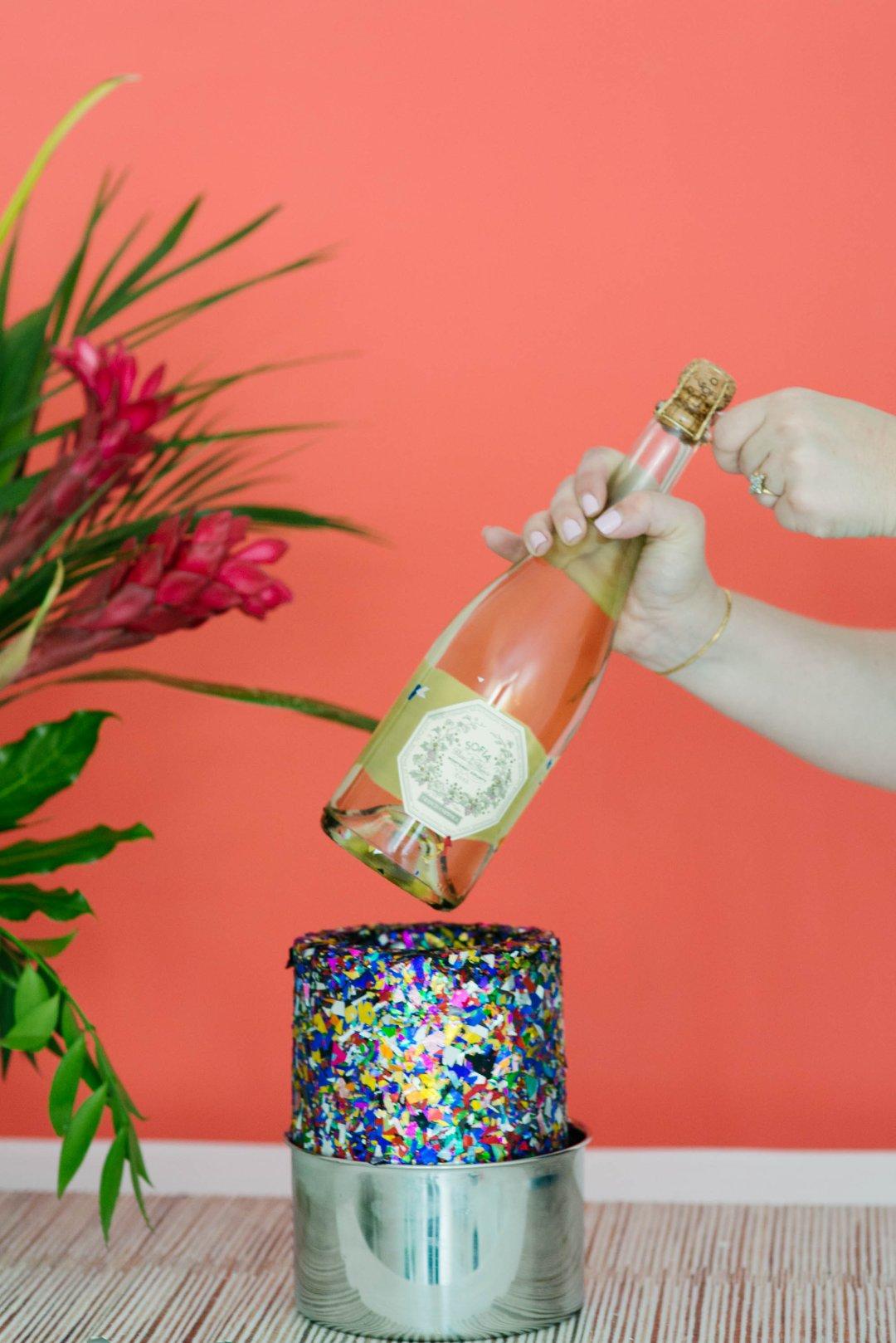 Hands popping champagne bottle out of confetti ice mold