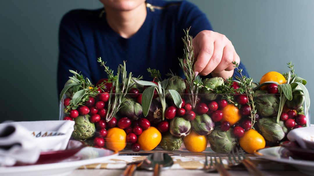 Arranging sprigs of fresh herbs in a clear centerpiece bowl of fruit and vegetables on a dining table