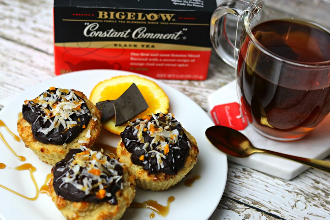 A plate of Keto Orange Muffins with orange chocolate glaze next to a glass of tea, and in front of a box of Bigelow Constant Comment