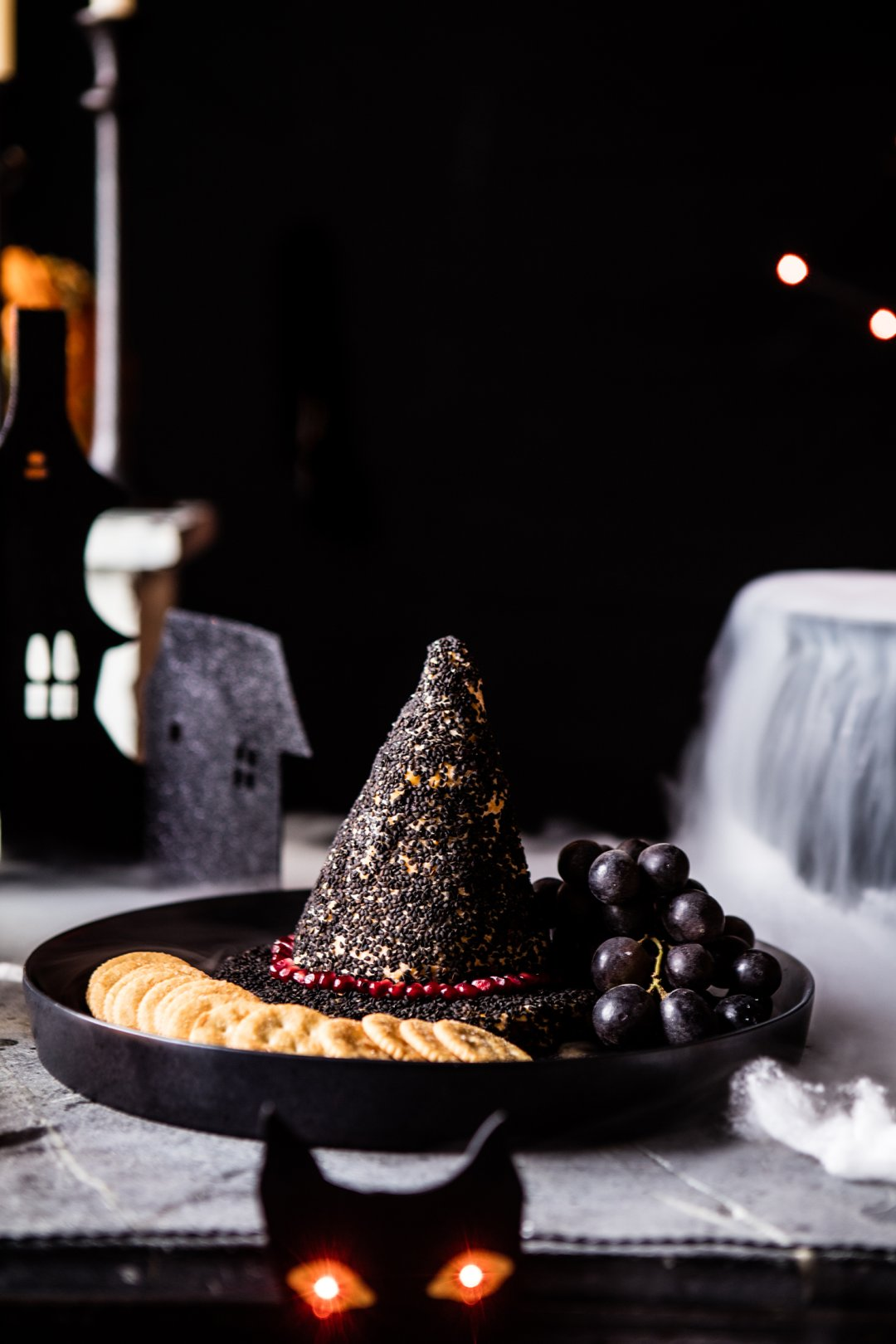 Black serving tray with cheese dip in the shape of a witch's hat surrounded by crackers, grapes and other snacks
